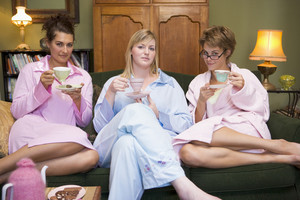 Three young women drinking tea together in their pyjamas