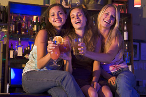Three young women sitting on a bar counter, toasting the camera