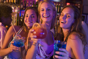 Three young women with drinks in a nightclub