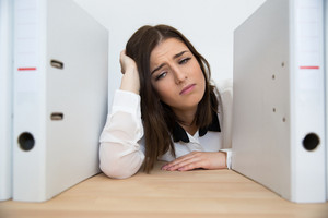 Tired businesswoman sitting the table with folders in office