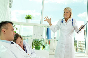 Tired clinicians in white coats sleeping in office while displeased doctor looking at them