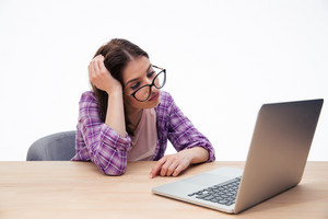 Tired female student sitting with laptop