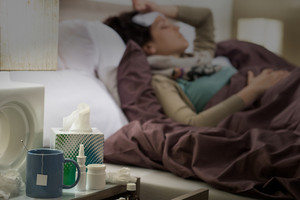 Tissue,flu medicines and tea on bedside table sick woman