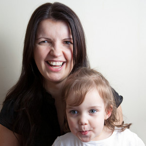 Toddler age girl sitting with her smiling mother while making funny monkey faces.