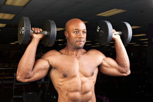 Toned and ripped lean muscle fitness man lifting weights.