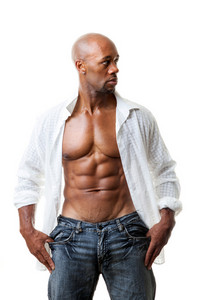 Toned and ripped lean muscle fitness man wearing an open shirt isolated over a white background.