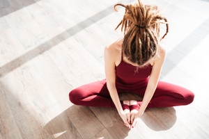 Top view of modern young woman with dreadlocks sitting and doing yoga on wooden floor