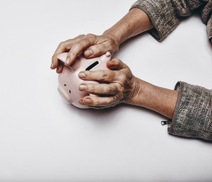 Top view of senior woman hands holding a piggy bank on grey surface. Elderly hands grabbing a small piggybank. Concept of secure investments.
