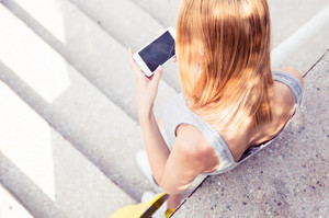 Top view portrait of a young girl using smartphone