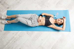 Top view portrait of a young woman lying on the yoga mat at gym