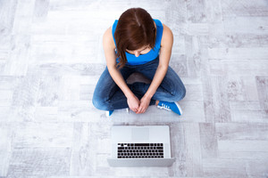Top view portrait of a young woman sitting on floor with laptop