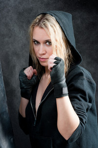 Tough boxing training woman in black grunge background