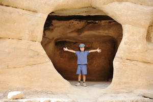 Tourist child posing in the rock hole, happy kid with a cap