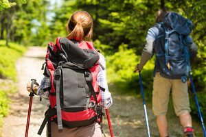 Tourist couple hiking in forest in summer