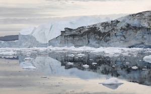 Towering, dirt-streaked iceberg reflected in icy waters under a grey sky