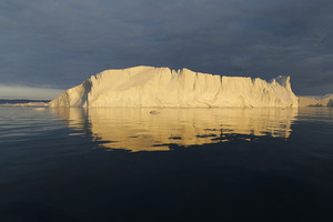 Towering iceberg bathed in golden sunlight against a dark sky