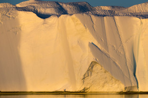 Towering iceberg cliff bathed in golden sunlight