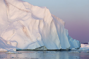 Towering iceberg in icy waters at dawn