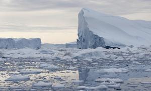 Towering iceberg in icy waters at dusk