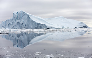 Towering iceberg reflected in clear water