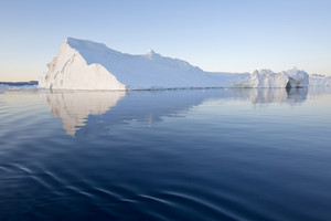 Towering iceberg reflected in icy waters at dawn