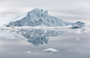 Towering iceberg reflected in icy waters under a grey sky