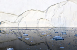 Towering iceberg reflected in icy waters