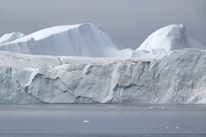 Towering iceberg under a grey sky