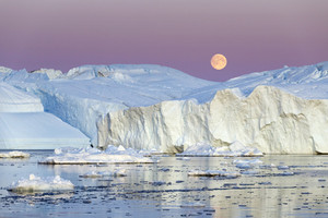 Towering icebergs and ice chunks against a full moon