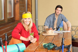 Tramping young couple backpack relax by wooden table drink water