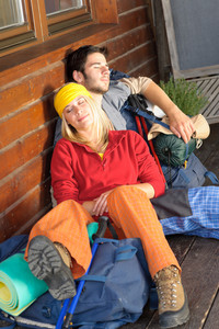 Tramping young couple backpack sleep sitting by wooden cottage