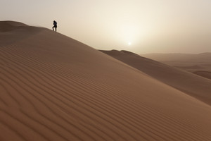 Traveler hiking to the top of a sunlit desert sand dune