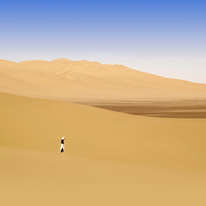 Traveler walking through a sandy desert