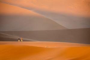 Travelers walking over sand dunes at sunset