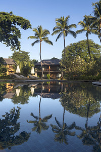 Tropical hotel reflected in a smooth swimming pool