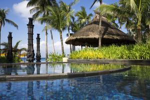 Tropical plants and beach umbrellas along a resort pool