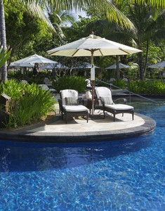 Tropical plants, beach umbrellas, and chairs along a resort pool