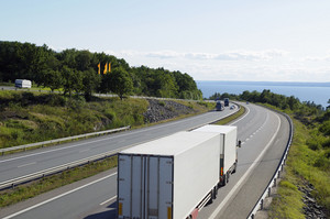 trucking on scenic freeway, sea in background