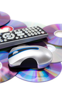 TV remote control and computer mouse on a pile of scattered dvd disks isolated over white.