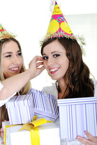 Two bautiful caucasian girls celebrating birthday wearing holiday hats
