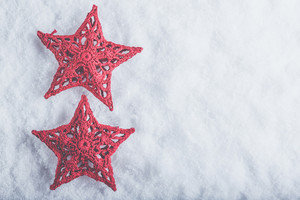 Two Beautiful magical vintage red stars on a white snow background. Winter and Christmas concept.