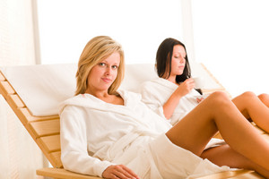 Two beautiful women relax sitting on sun-beds healthy luxury spa