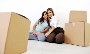 Two beautiful young woman in the room with boxes for moving