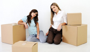 Two beautiful young woman smiling in the room with boxes for moving