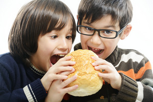 Two boys eating bread