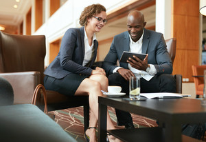 Two business people sitting at coffee shop discussing project on digital tablet. Young businesswoman and businessman looking at tablet computer smiling.
