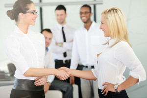 Two business women handshaking after the female deal is done