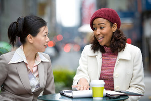 Two business women having a casual meeting or discussion in the city.
