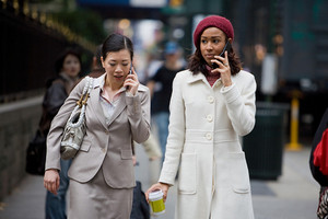 Two business women having conversations on their cell phones while walking in the big city.