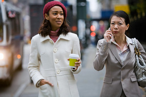 Two business women walking in the big city. One is on her phone.